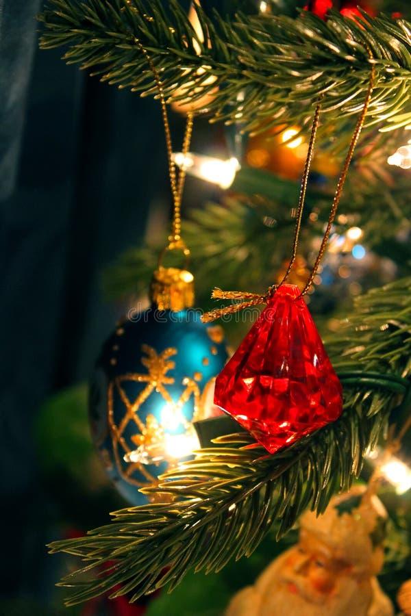Czerwoni biżuteryjni boże narodzenia ornamentują obwieszenie na drzewie wśród innych zdjęcie stock