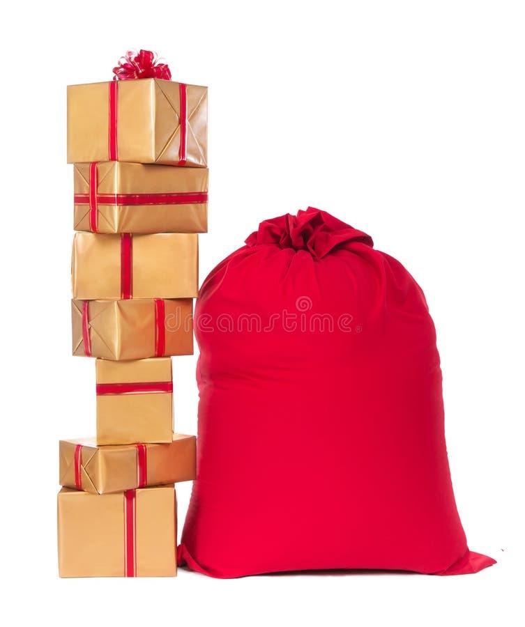 Czerwoni boże narodzenia grabiją i stos prezenty, odizolowywający na białym backgrou zdjęcie stock