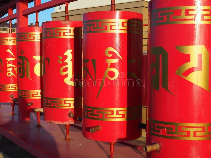 Czerwoni Buddyjscy modlitewni koła z Złotym tekstem modlitwy w sanskrycie iluminującym światłem słonecznym fotografia royalty free