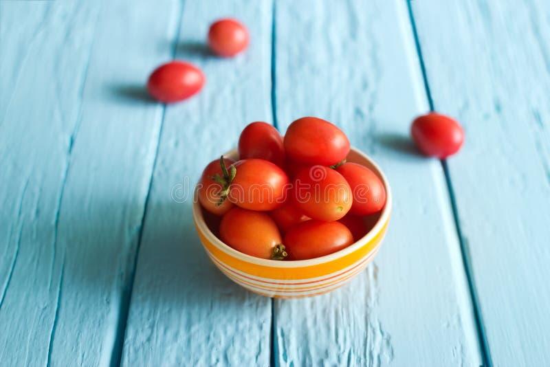 Czerwoni czereśniowi pomidory w pucharze na błękitnym drewnianym tle fotografia stock