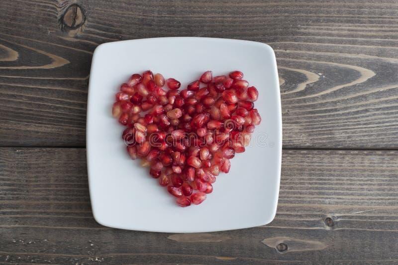Czerwoni granatowów ziarna w kształcie serce w naczyniu zdjęcia royalty free