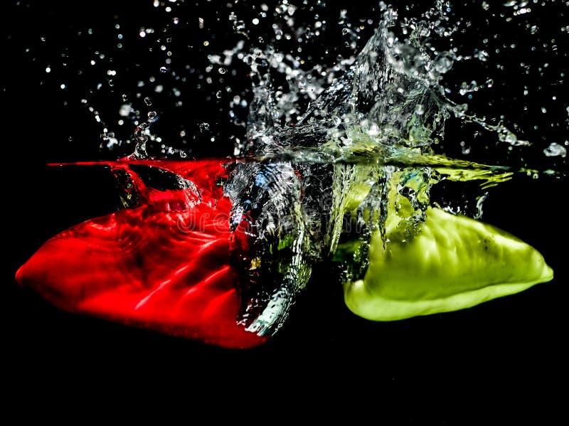 Czerwoni i zieleni pieprze robi wodnemu pluśnięciu obraz royalty free