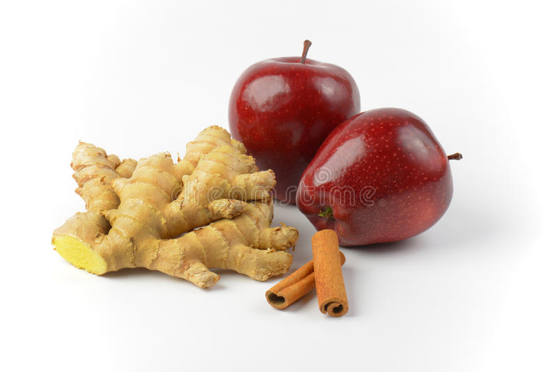 Czerwoni jabłka, imbir kije, korzeniowi i cynamonowi fotografia stock