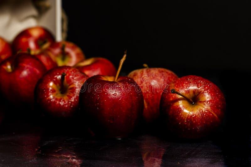 Czerwoni jabłka na czerni zgłaszają i krople woda obraz royalty free
