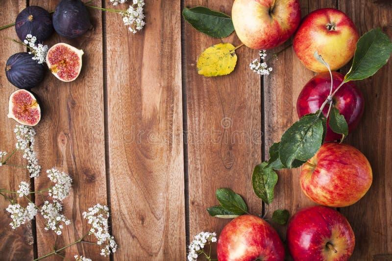 Czerwoni jabłka na drewnianym pudełku z liśćmi i kwiatami Jesieni żniwo owoc Odgórny widok Uwalnia przestrzeń dla teksta obraz stock