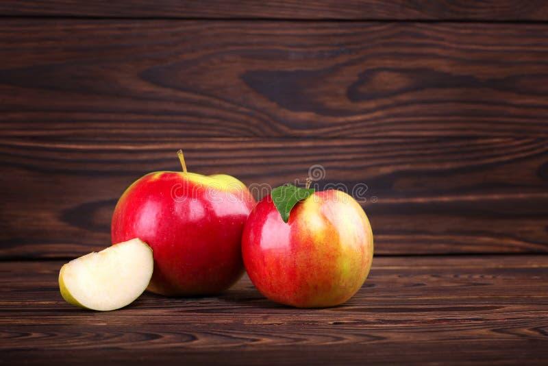 Czerwoni jabłka na drewnianym stołowym tle Słodcy i smakowici rżnięci jabłka piękne jabłka Słodkie jarosz przekąski Sezonowe owoc zdjęcie royalty free