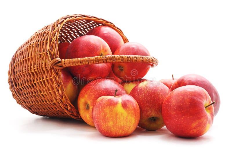 Czerwoni jabłka opuszczający z kosza zdjęcie stock
