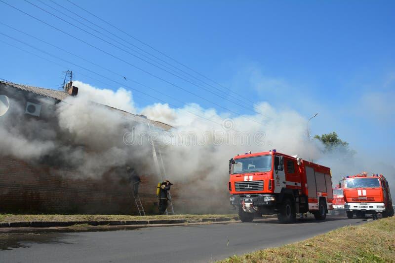 Czerwoni kolorowi firetrucks jadą na wywoławczym pożarniczym stłumieniu Pożarnicza szkoda i strażacy Domowy pali puszek płonący d zdjęcie stock