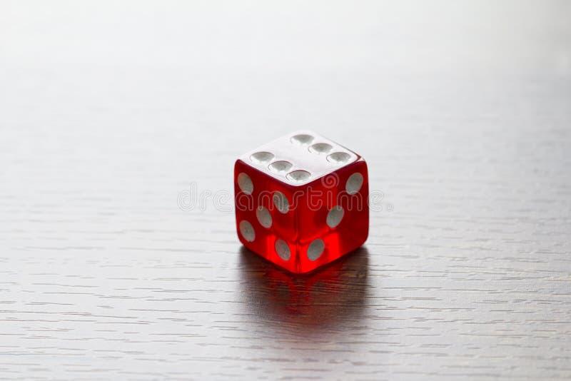 Czerwoni kostka do gry odizolowywający na drewnianym desktop zdjęcie royalty free