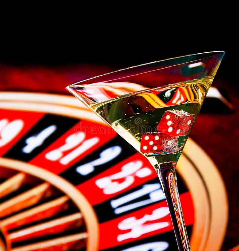 Czerwoni kostka do gry w koktajlu szkle przed ruletowym kołem zdjęcie royalty free