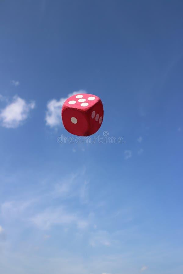 Czerwoni kostka do gry zawieszający w niebie zdjęcia stock