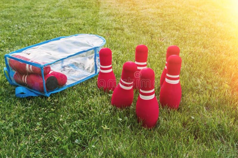 Czerwoni kręgle Lato dziecko ' Na zielonej trawie w centrum rama są zabawki dla dzieci obrazy stock