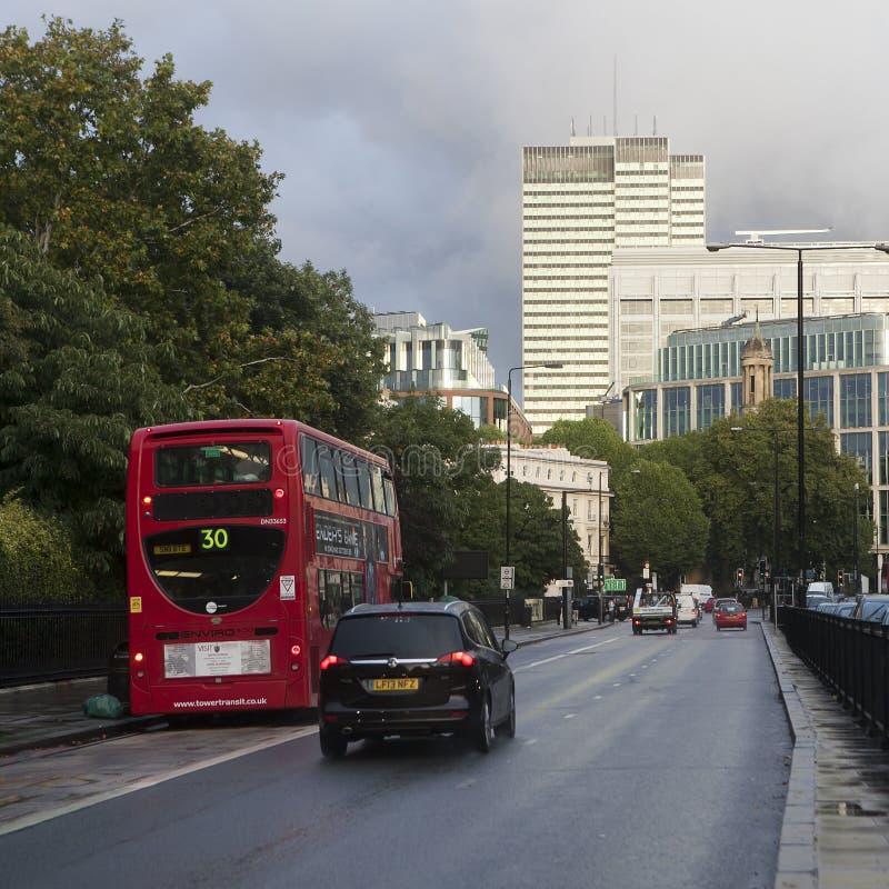 Czerwoni Londyńscy autobusy podczas godziny szczytu w środkowym Londyn bierze pasażerów do i z pracy i robi zakupy krzyżujący pud zdjęcie stock