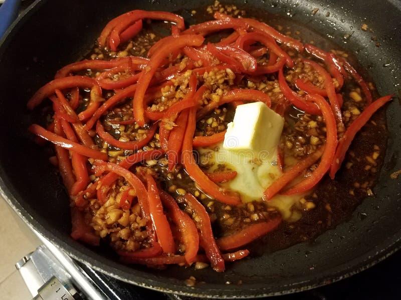 Czerwoni pieprze, czosnek i masło w smażyć nieckę zdjęcia royalty free