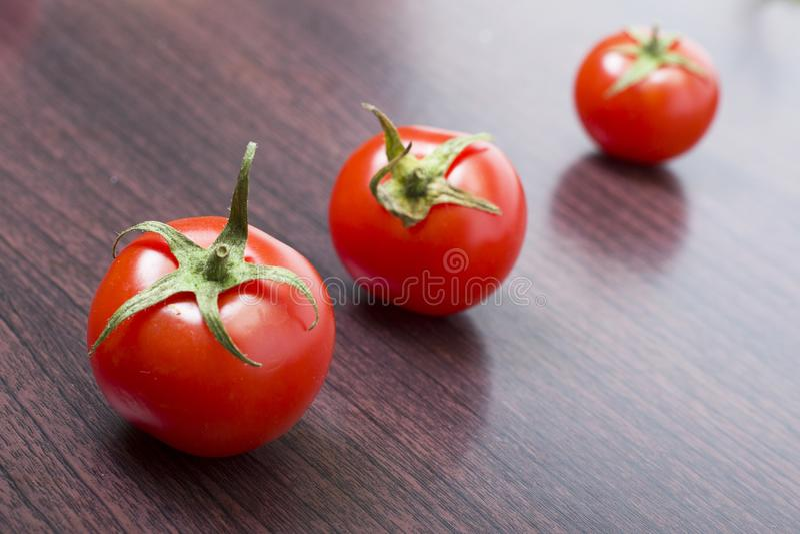Czerwoni pomidory na drewnianym brązu stole Trzy czerwonego czereśniowego pomidoru obrazy stock