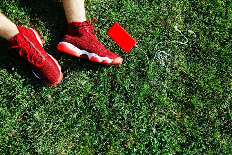 Czerwoni sneakers, telefon i walkmans na smole, zdjęcia royalty free