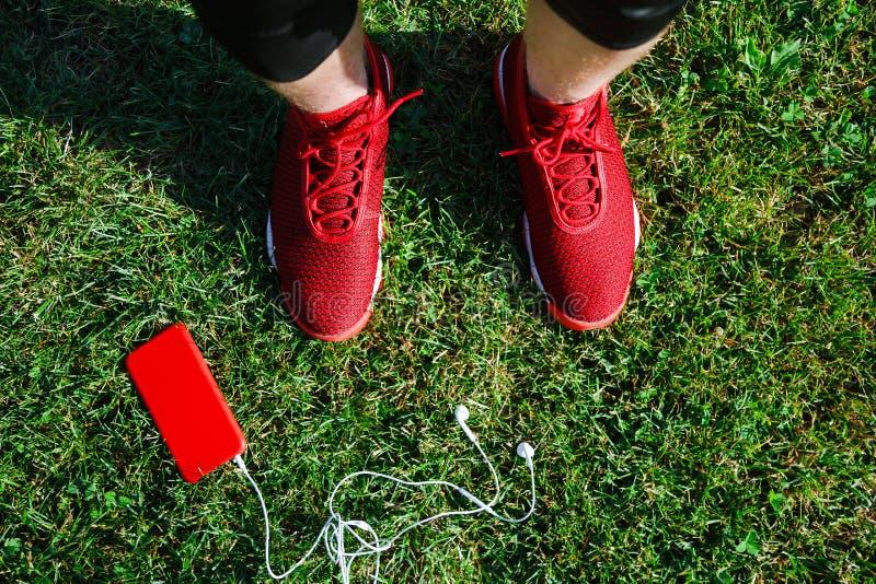 Czerwoni sneakers, telefon i walkmans na trawie, fotografia royalty free
