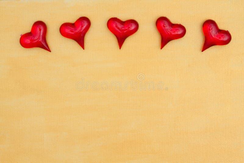Czerwoni szklani serca na ręce malowali zakłopotanego złocistego tło obrazy stock