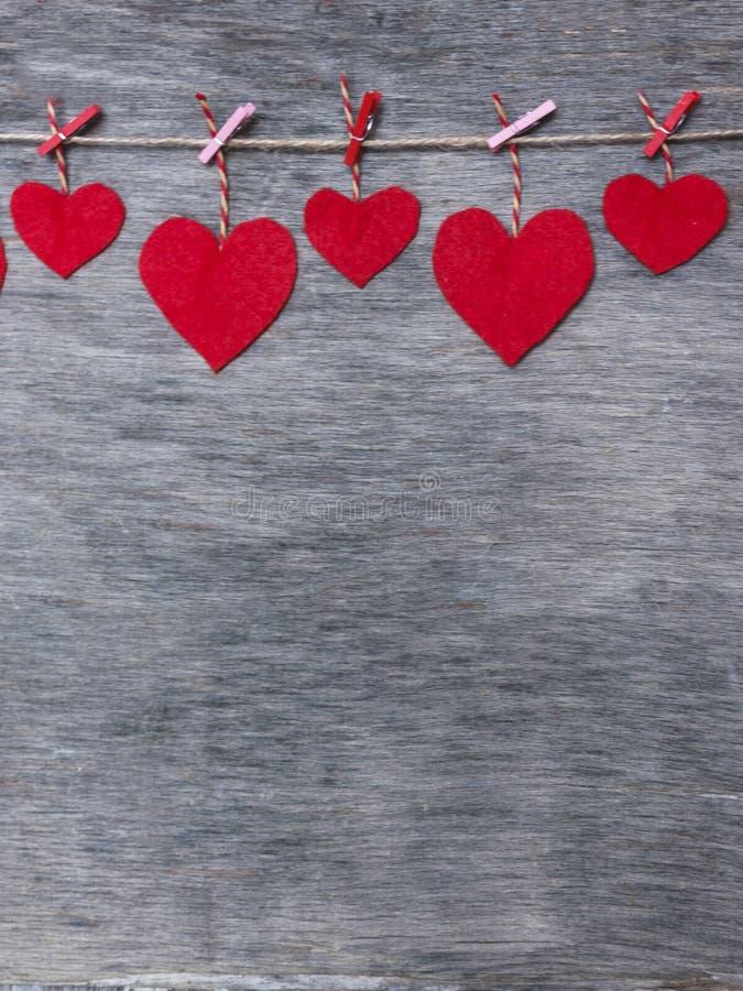 Czerwoni walentynki miłości serca na naturalnych sznura i menchii szpilkach wiesza na nieociosanym driftwood tekstury tle, kopii  zdjęcia stock