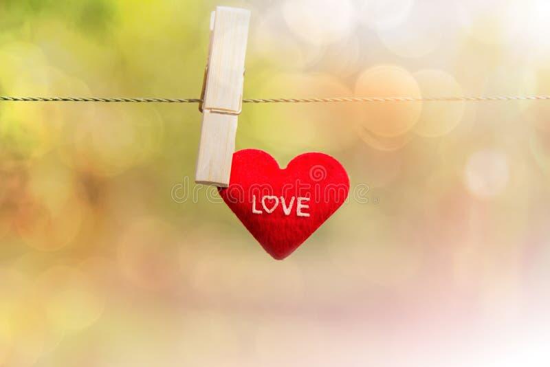 Czerwoni walentynki ` s serca na linowych sznura i drewna klamerkach wiesza na ru zdjęcie stock
