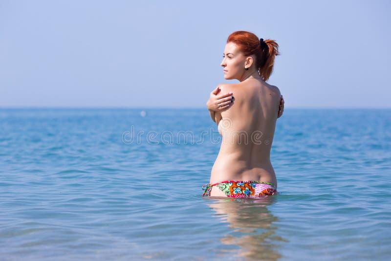 Czerwoni z włosami młoda kobieta stojaki w wodzie morskiej himself i obejmowaniu zdjęcie stock