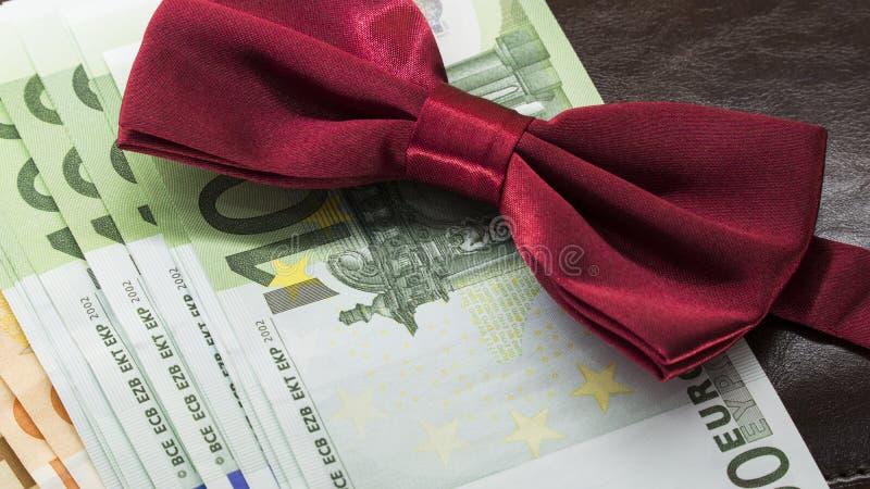 Czerwony łęku krawat przeciw tłu euro pieniądze zdjęcia royalty free
