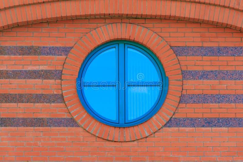 Czerwony ściana z cegieł z round glassed okno obraz stock