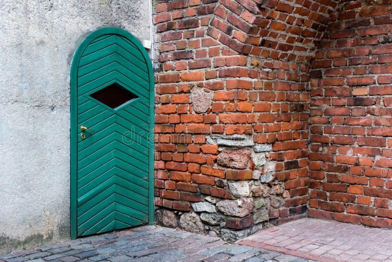 Czerwony ściana z cegieł z zielonym drzwi zdjęcie royalty free