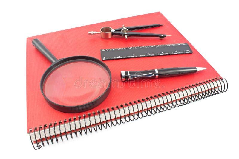 Czerwony ślimakowaty notatnik z rysunkowym kompasem, władcą i magnifier, jest obrazy royalty free