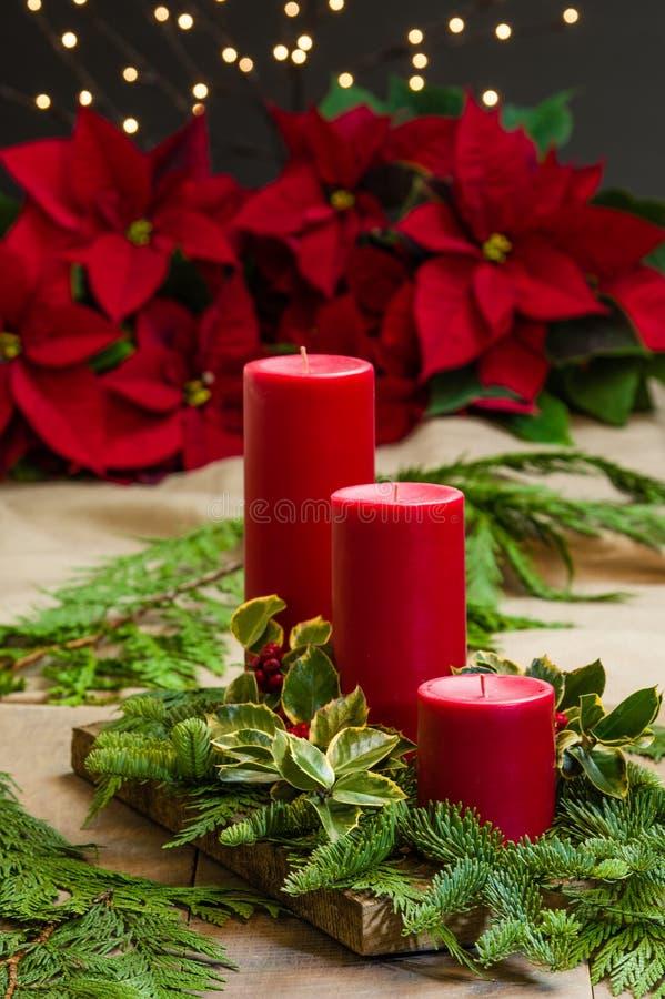 Czerwony świeczki centerpiece z zieleniami fotografia stock