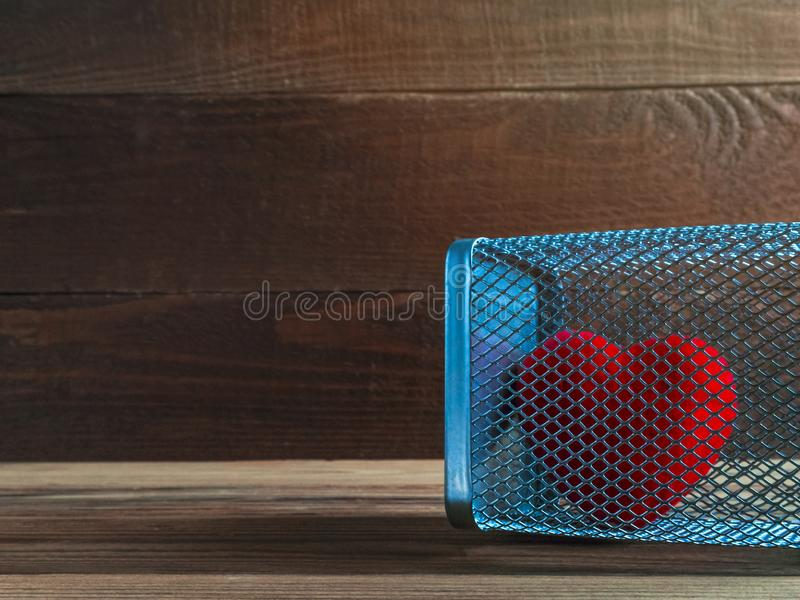 Czerwony Aksamitny serce w siatki klatce na Nieociosanym Drewnianym tle Miłość, pojęcie, Domowy przemocy, samotności, wolności i  obrazy stock