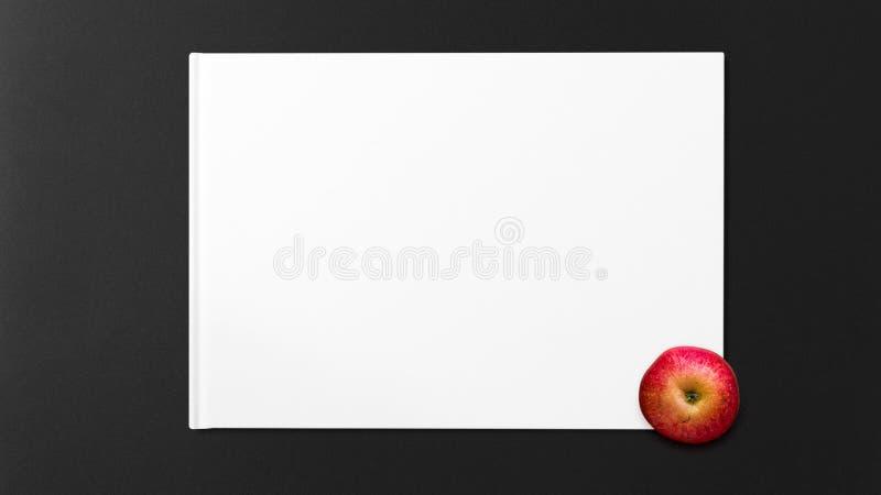 Czerwony Apple na białej księdze na ciemnym tle obrazy royalty free