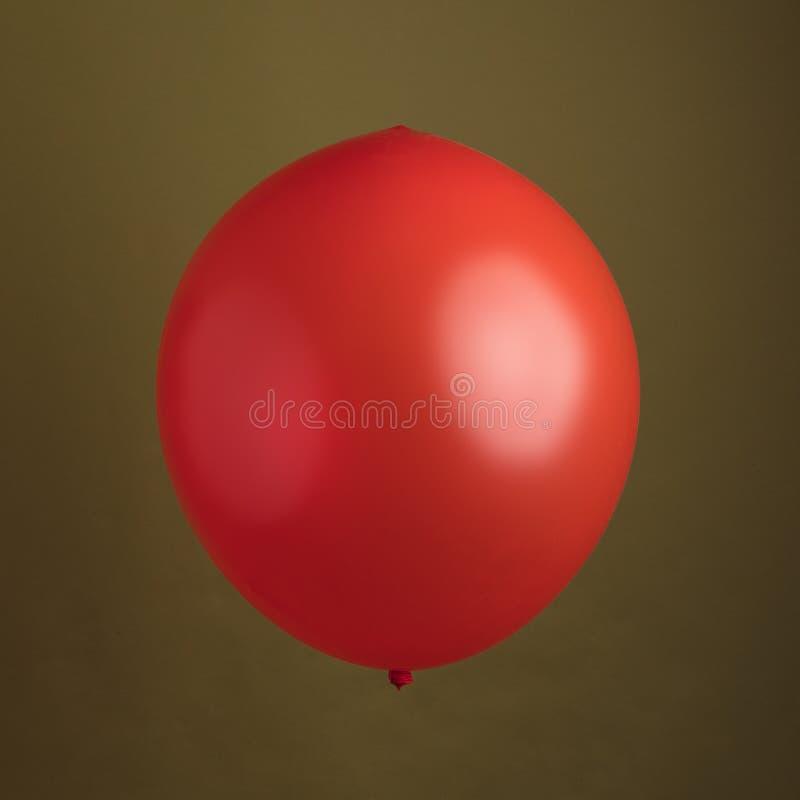 Czerwony Błyszczący balon Przeciw Oliwnej zieleni tłu obraz royalty free