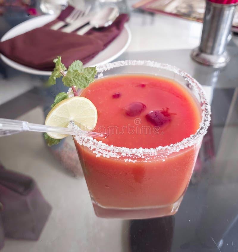 Czerwony barwiony mocktail z lodem wokoło szkła i cytryny mennicy polewy fotografia royalty free