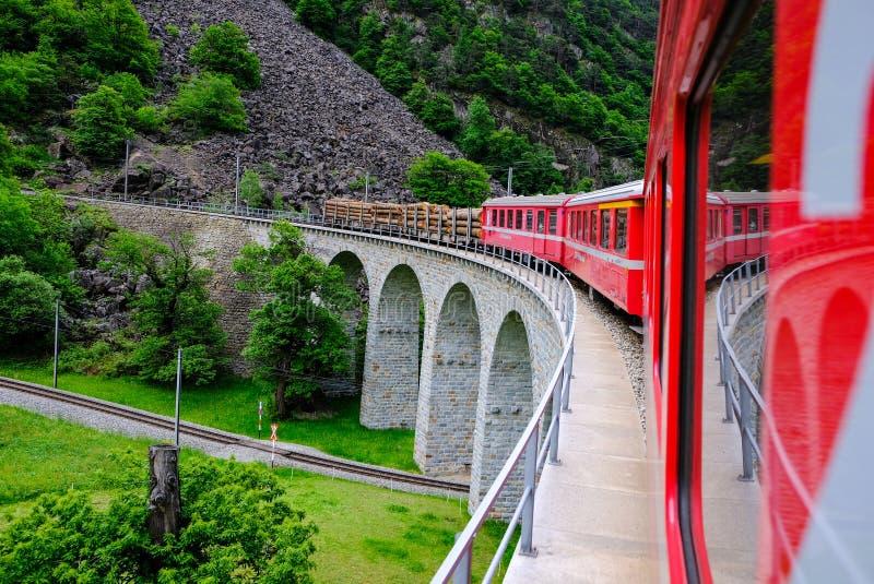 Czerwony Bernina pociąg podróżuje na bardzo sławnym wiadukcie obrazy royalty free