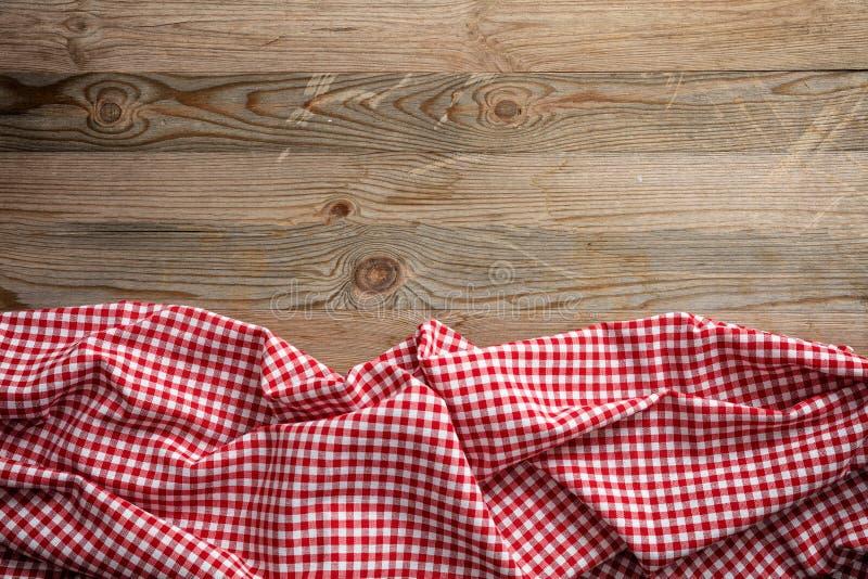 Czerwony biały w kratkę pykniczny tablecloth na drewnianym tle, kopii przestrzeń obraz royalty free