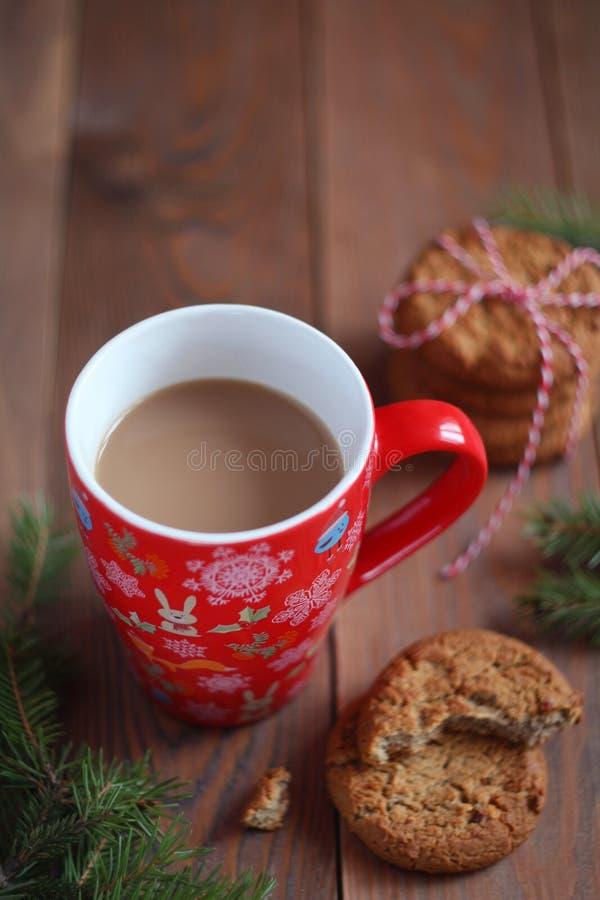 Czerwony Bożenarodzeniowy kubek kawa i ciastka na drewnianym stole zdjęcia stock