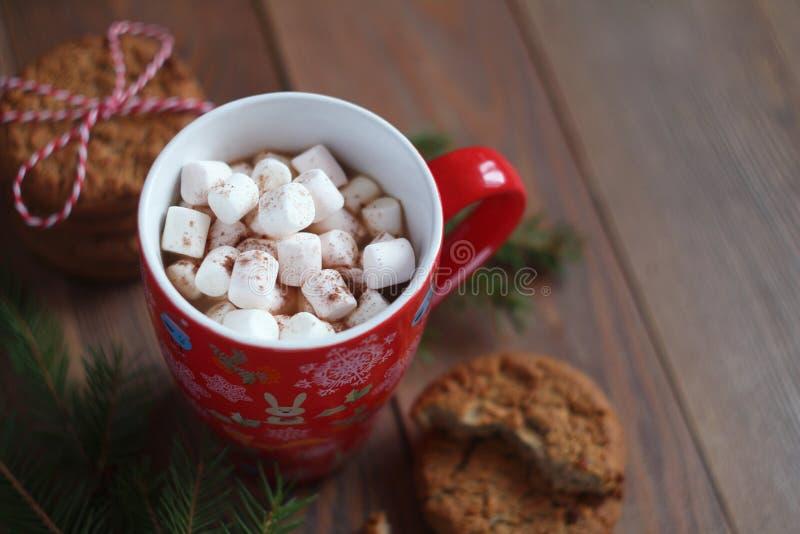 Czerwony Bożenarodzeniowy kubek kawa, marshmallows i ciastka na drewnianym stole fotografia stock