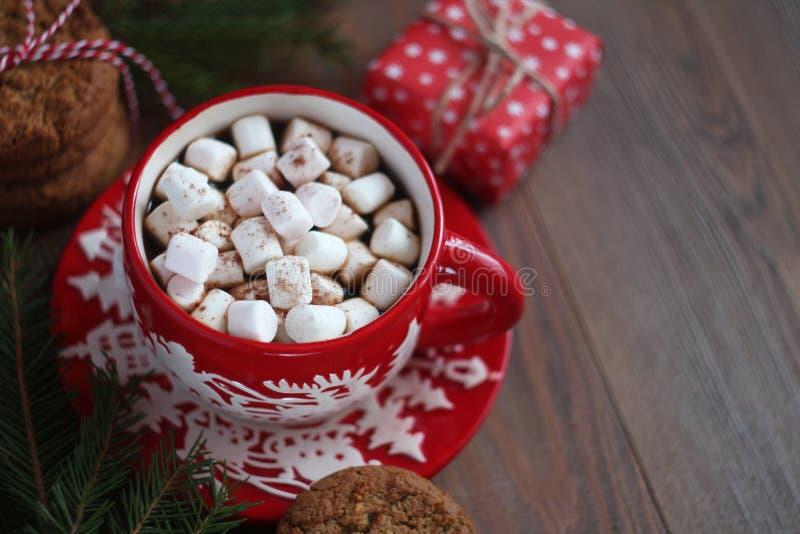 Czerwony Bożenarodzeniowy kubek kawa, marshmallows i prezenta pudełko na drewnianym stole fotografia royalty free