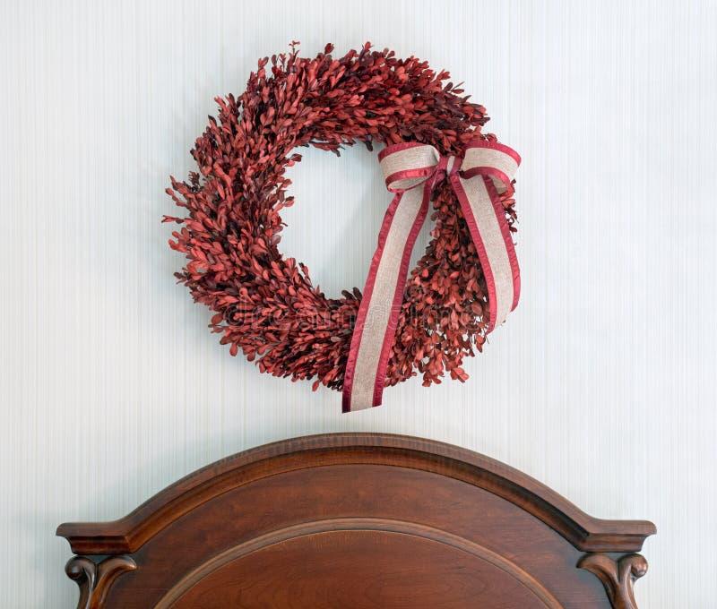 Czerwony Boxwood wianek nad Drewniany Headboard fotografia stock