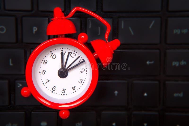 Czerwony budzik kłama na laptop klawiaturze obrazy royalty free