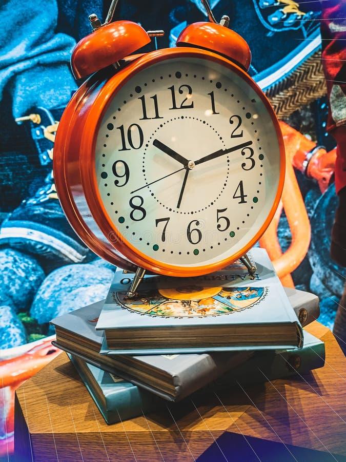 Czerwony budzik na stosie książki Nauki pojęcie zdjęcia stock