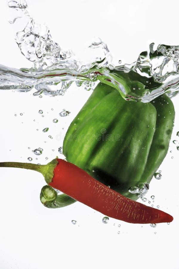 Czerwony Chili i zielony pieprz opuszczaliśmy w wodę zdjęcia stock