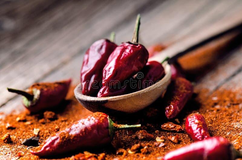Czerwony chili pieprze, korzenni na drewnianej łyżce Warzywo na zmroku, drewniany stół Pojęcie gorący jedzenie obrazy stock