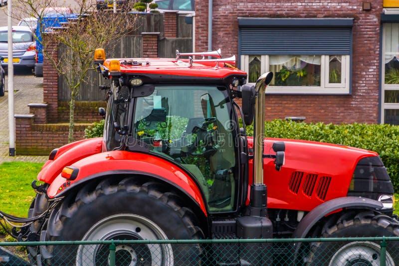 Czerwony ciągnik parkujący w obszarze zamieszkałym, wieś transportu tło, chłop odwiedza wioskę zdjęcia royalty free