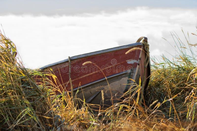Czerwony czółno dokujący w wysokiej trawie obrazy stock