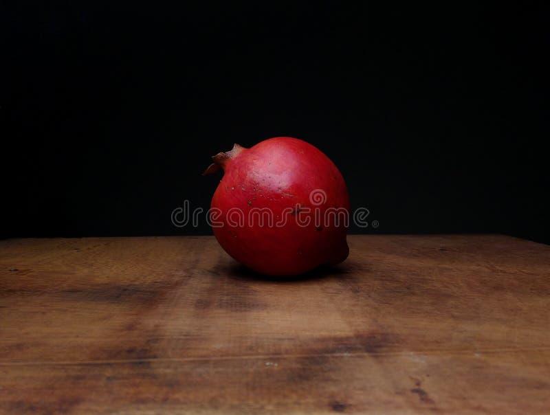 Czerwony dojrzały granatowiec na stole drewnianym obraz stock