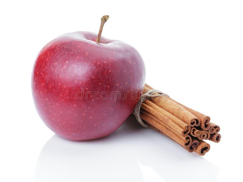 Czerwony dojrzały jabłko i cynamonowi kije obrazy stock