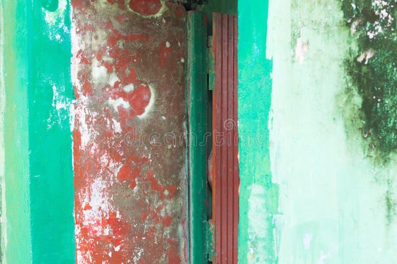 Czerwony drewniany drzwi i zielona ściana - wejście zaniechany dom obraz royalty free