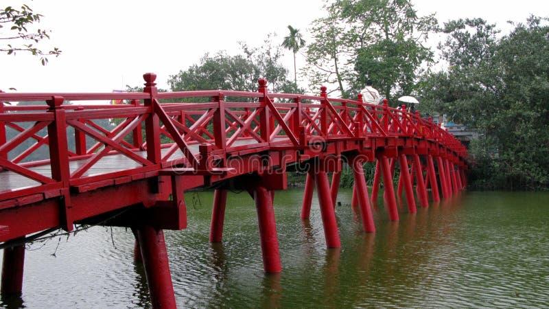 Czerwony drewniany most błękitnym jeziorem zdjęcie stock